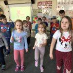 Grupa dzieci gimnastykująca się na dywanie, w sali przedszkolnej.