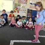 Dziewczynka idąca w sali przedszkolnej wyznaczoną trasą, w tle grupa dzieci siedząca na dywanie. Dziewczynki mają na głowie owocowe opaski.