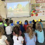 Grupa dzieci siedzących na dywanie w sali przedszkolnej i oglądających bajkę wyświetlaną na tablicy interaktywnej. Dziewczynki maja na głowach owocowe opaski.