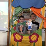 Dwoje chłopców trzymających w ręku kukiełki i przedstawiających teatrzyk.