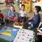 Sześcioro dzieci siedzących na dywanie w sali przedszkolnej. Przed dziećmi znajduje się skrzynka z owocami oraz mata ilustrująca piramidę zdrowego żywiania.