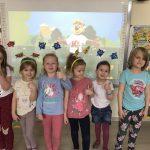 Sześć dziewczynek pozujących do zdjęcia w sali przedszkolnej. W tle znajduje się tablica interaktywna, na której wyświetlona jest bajka. Dziewczynki mają na głowie owocowe opaski.