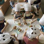 Sześcioro dzieci ubranych w fartuszki i czapki kucharskie siedzący przy stolikach, na których znajdują się talerze i owoce. Dzieci wykonują owocowe szaszłyki.