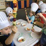 Dzieci ubrane w fartuszki i czapki kucharskie siedzące przy stolikach na których znajdują się talerze i owoce. Dzieci trzymają w rękach owocowe szaszłyki.