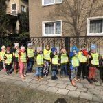 Grupa dzieci spacerująca po dworze ubrana w kamizelki odblaskowe.
