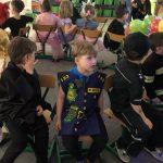 Grupa dzieci siedzących w kole na krzesłach w sali. Dzieci ubrane są w karnawałowe stroje.