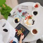 Dziecko mające na głowie czapkę kucharską siedzące przy stole, na którym znajdują się talerze i miseczki z owocami. Dziecko układa na talerzu owocową sowę.
