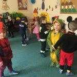 Dzieci tańczące w sali przedszkolnej. Każde dziecko ma ubrane strój karnawałowy.