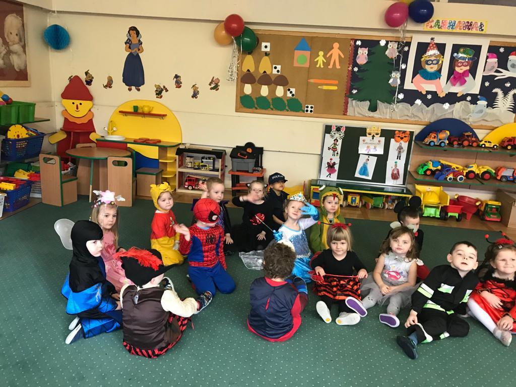 Grupa dzieci siedzących na dywanie w sali przedszkolnej. Każde dziecko ubrane jest w karnawałowy strój.