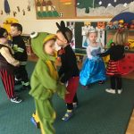 Sześcioro dzieci tańczących w sali przedszkolnej. Każde dziecko jest ubrane w karnawałowy strój.