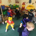Dziewięcioro dzieci tańczących w sali przedszkolnej. Dzieci ubrane są w karnawałowe stroje.