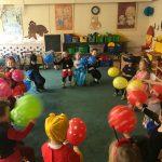 Grupa dzieci siedzących w sali przedszkolnej, w kole na krzesłach. Każde dziecko ubrane jest w strój karnawałowy i trzyma w rękach balona.