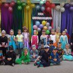 Grupa dzieci ubrana w karnawałowe stroje, pozująca do zdjęcia w dwóch rzędach. Dzieci w pierwszym rzędzie siedzą na dywanie, w drugim stoją. W tle znajduje się dekoracja składająca się z balonów i kolorowych pasków bibuły.