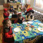 Dzieci siedzące przy stolikach w sali przedszkolnej. Przedszkolaki ubrane są w karnawałowe stroje, na stołach znajdują się talerze oraz ciastka i cukierki.
