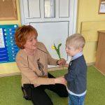 Chłopiec trzyma wicuągiętą rękę z tulipanem w stronę Pani, która kuca.