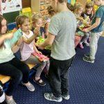 4 dziewczynki siedzą w rzędzie na krzesłach. Pod jedną z nich stoi chlopiec, który trzyma w rękach koszyczek z cukierkami.