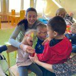 Chłopiec trzyma wicuągiętą rękę z tulipanem w stronę dziewczynki, która siedzi. Za dziewczynką siedzi nauczycielka, a obok chłopiec.