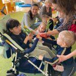 Chłopiec trzyma wicuągiętą rękę z tulipanem w stronę dziewczynki, która siedzi na wózku. Za chłopcem stoi nauczycielka, która trzyma melatowe serduszko.