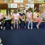 dziewczynki siedzą w rzędzie na krzesłach. Na kolanach mają zapakowane torebki z prezentem , które otwierają.