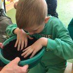 Chłopiec dotyka ziemi, która znajduje się w misce przed nim.