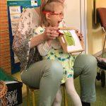 Dziewczynka stoi przed nauczycielką. W rękach trzymają tabliczkę z pomalowaną na zielono kartką, a w drugiej ręce pędzel.