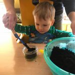 Chłopiec siedzi przy stoilku. Trzyma razem z nauczycielką łopatkę. Razem wsypują ziemię do małego słoiczka.