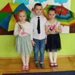 3 dzieci ( jeden chhłopiec po środku i dwie dziewczynki) stoją. Dziewczynki trzymają w ręce kolorowe parasole