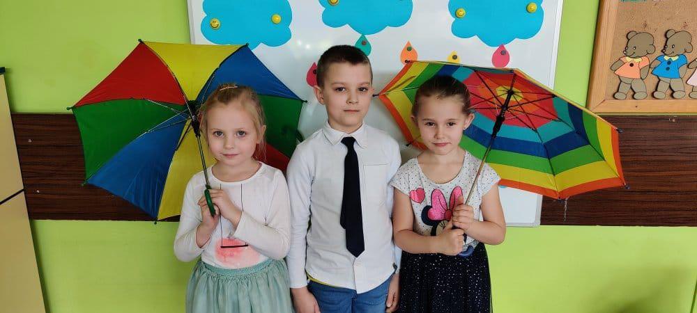 3 dzieci ( jeden chłopiec po środku i dwie dziewczynki) stoją. Dziewczynki trzymają w ręce kolorowe parasole