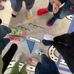 Sześć osób stojących na dywanie w kolorowych, różnych skarpetkach.