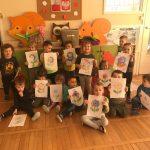 Grupa dzieci pozujących do zdjęcia w sali przedszkolnej i trzymających w rękach kolorowanki.