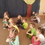Grupa dzieci siedzących na dywanie w trzech rzędach.
