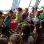 Grupa dzieci stojących przy stołach i sadzących wiosenne kwiatki. Na stole znajdują się kolorowe doniczki, nasiona oraz sadzonki kwiatów.