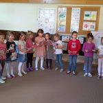 Grupa dzieci stojąca w sali przedszkolnej i trzymająca w rękach prezenty. w półkolu