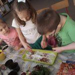 Troje dzieci siejące nasiona rzeżuchy na tacce z watą.