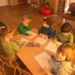 Pięcioro dzieci siedzących przy stoliku i kolorujących kolorowanki.