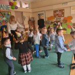 Grupa dzieci tańczących w sali przedszkolnej wraz z dwoma Paniami. Dzieci mają na głowach ubrane kolorowe czapeczki