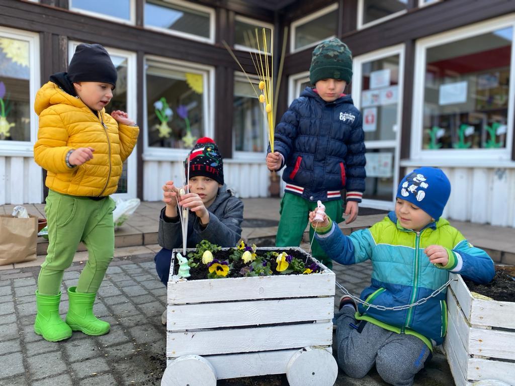 Czterech chłoców sadzących do drewnianego wagonika bratki oraz trzymających ozdoby wielkanocne.