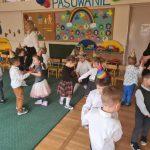 Grupa dzieci tańczących w parach w sali przedszkolnej wraz z dwoma Paniami. Dzieci mają na głowach ubrane kolorowe czapeczki.