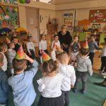 Grupa dzieci stojąca na dywanie, w sali przedszkolnej wraz z dwoma Paniami. Dzieci mają na głowach kolorowe czapki. Wszyscy ustawieni są w kole.
