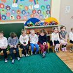 Grupa dzieci siedząca w sali przedszkolnej, w rzędzie na krzesłach.