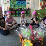 Pięć dziewczynek mających na głowach różowe opaski - korony, siedzące na dywanie i mające zamknięte oczy. Przed nimi, na podłodze stoi ozdobiony kwiatami kosz z upominkami.