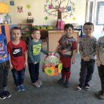 Sześcioro chłopców stojących w jednym rzędzie w sali przedszkolnej. Dwóch chłopców stojących po środku trzyma w rękach kosz ozdobiony kolorowymi kwiatami, w którym znajdują się upominki.