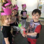 Po lewej stronie stoi pięć dziewczynek, mających na głowach różowe opaski-korony. Dziewczynka na końcu trzyma w ręce upominek. Po prawej stronie Chłopiec wręcza dziewczynce upominek.