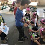 Po prawej stronie cztery dziewczynki mające na głowie opaski - korony siedzące na dywanie i trzymające w rękach upominki oraz dyplomy. Naprzeciw nich stoją chłopcy, którzy wręczają dziewczynkom dyplomy oraz upominki.