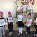 Pięć dziewczynek mających na głowach różowe opaski-korony stojące w jednym rzędzie w sali przedszkolnej. Każda dziewczynka trzyma w rękach upominek oraz dyplom.