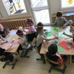 Po lewej stronie pięć dziewczynek mających na głowach różowe opaski - korony wykonują przy stolikach prace plastyczne - kwiatki. Po prawej stronie sześcioro chłopców siedzących przy stoliku i wykonujących prace plastyczne- kwiatki.