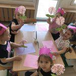 Pięć dziewczynek mających na głowach różowe opaski - korony, siedzące przy stoliku i trzymające w rękach prace plastyczne - kwiatki.
