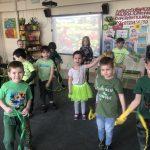 Grupa dzieci tańcząca w rozsypce w sali przedszkolnej i trzymająca w rękach kolorowe paski bibuły.