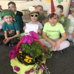 Dziewięcioro dzieci siedzących w sali przedszkolnej w dwóch rzędach.Dzieci w pierwszym rzędzie siedzą na dywanie. Dziewczynka siedząca w środku ma założone przeciwsłoneczne okulary i wiosenny kapelusz. Chłopiec siedzący po lewej stronie ma na głowie czapkę - żabkę. Chłopiec po prawej stronie ma na głowie czapkę - bociana. Chłopcy siedzacy w drugim rzędzie mają naszyjach naszyjniki z kwiatów, dziewczynki wiosenne opaski. Przed dziećmi stoi koszyk z ziołami i kwiatkami.