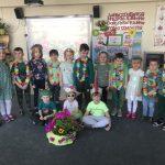 Grupa dzieci pozujących do zdjęcia w dwóch rzędach. Dzieci w pierwszym rzędzie siedzą na dywanie. Dziewczynka siedząca w środku ma założone przeciwsłoneczne okulary i wiosenny kapelusz. Chłopiec siedzący po lewej stronie ma na głowie czapkę - żabkę. Chłopiec po prawej stronie ma na głowie czapkę - bociana. Chłopcy stojący w drugim rzędzie mają naszyjach naszyjniki z kwiatów, dziewczynki wiosenne opaski. Przed dziećmi stoi koszyk z ziołami i kwiatkami.